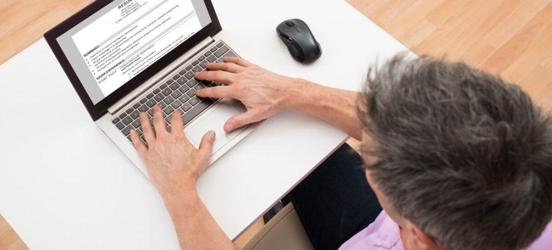 Man writing resume on laptop
