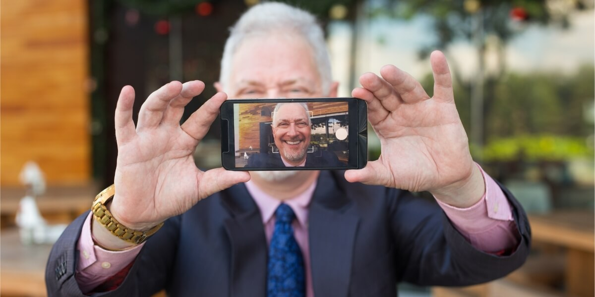 Businessman taking LinkedIn profile picture selfie