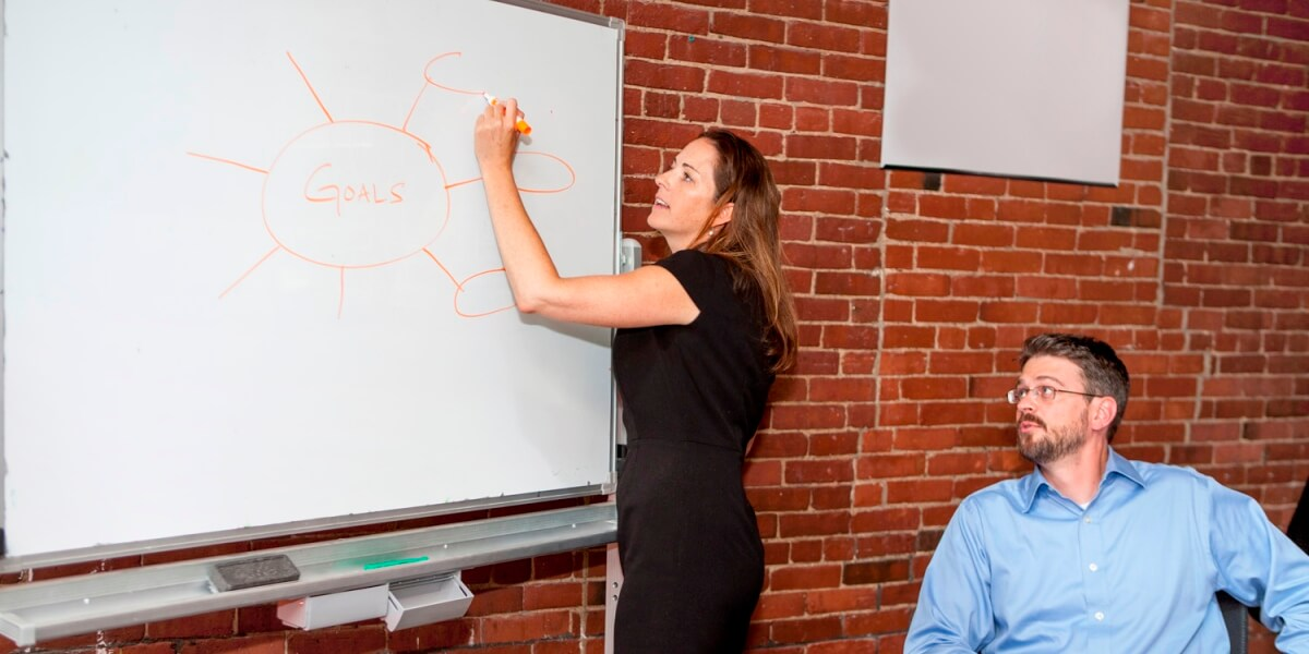 Outplacement services coach writes the word goals on a whiteboard while colleague watches